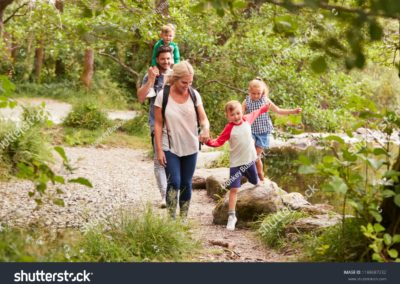 stock-photo-family-hiking-along-path-by-river-in-uk-lake-district-1188687232-min