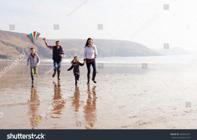 stock-photo-family-running-along-winter-beach-flying-kite-208005655-min