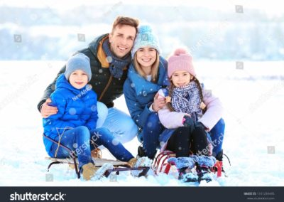 stock-photo-happy-family-with-sledges-outdoors-during-snowfall-winter-vacation-1161234445-min
