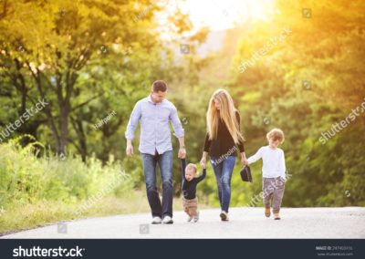stock-photo-happy-young-family-walking-down-the-road-outside-in-green-nature-247460416-min