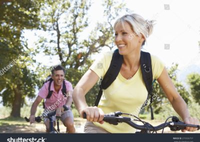 stock-photo-middle-aged-couple-cycling-through-countryside-279906797-min