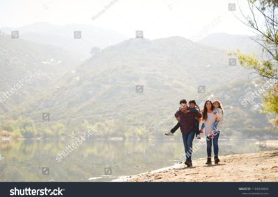 stock-photo-parents-piggybacking-their-young-children-by-a-mountain-lake-1184948896-min