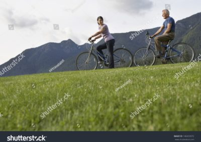stock-photo-side-view-of-a-middle-aged-man-and-woman-biking-on-landscape-with-mountain-range-in-the-background-146603972-min