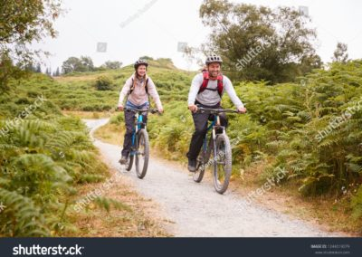 stock-photo-young-adult-couple-riding-mountain-bikes-in-the-countryside-full-length-1244019079-min